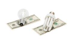L'energia salva la lampada contro la lampadina su soldi Immagine Stock