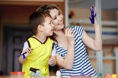 L'enfance curieux, un petit garçon jouant avec sa mère, dessine, des peintures sur les paumes Photo stock