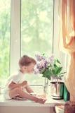 L'enfant à un hublot Image stock