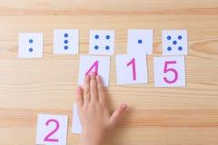 L'enfant écarte des cartes avec des nombres aux cartes avec des points L'étude des nombres et des mathématiques Photographie stock libre de droits