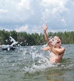 L'enfant éclabousse de l'eau autour d'une plongée de nageur dans l'eau enfant excité au sujet de la natation Photo libre de droits