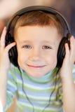 L'enfant écoute la musique par l'intermédiaire des écouteurs photo stock