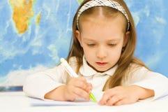 L'enfant écrit dans l'école maternelle Images libres de droits