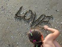 L'enfant écrit le mot AMOUR sur la plage Photographie stock libre de droits