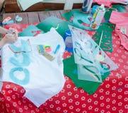 L'enfant écrit les lettres dans l'hébreu sur un T-shirt blanc Images stock