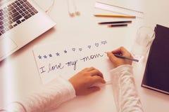 L'enfant écrit un message de jour de mères Photographie stock libre de droits