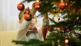 L'enfant élégant heureux avec le noeud papillon décorent l'arbre de Noël, garçon de sourire se préparent à la célébration de la j banque de vidéos