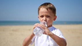 L'enfant a été servi une bouteille de l'eau après quoi il a commencé à boire l'eau sur la plage sablonneuse de mer banque de vidéos