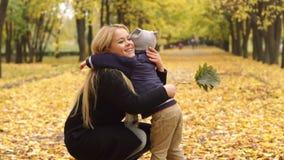 L'enfant étreint doucement sa mère en parc d'automne banque de vidéos