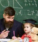 L'enfant étudie avec le professeur, écoutant avec l'attention Concept d'éducation élémentaire Professeur et élève dans la taloche image stock