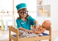 L'enfant adorable avec des vêtements de docteur joue avec la poupée Image libre de droits