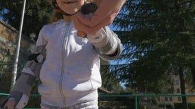 L'enfant apprend à monter des patins de rouleau banque de vidéos