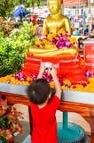 L'enfant arrosent l'eau sur une image de Bouddha Photo libre de droits