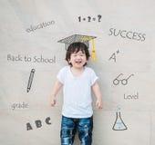 L'enfant asiatique heureux de plan rapproché avec le visage de sourire avec l'icône mignonne sur le mur en pierre de marbre a don Images libres de droits
