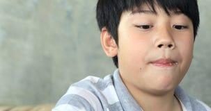 L'enfant asiatique heureux ont plaisir à manger de la salade avec le visage délicieux banque de vidéos