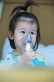 L'enfant asiatique tient un inhalateur de vapeur de masque pour le traitement de l'asthme Photos stock