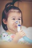 L'enfant asiatique tient un inhalateur de vapeur de masque pour le traitement de l'asthme Images stock
