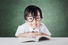 L'enfant attirant lit le livre sur le bureau dans la classe Photos libres de droits
