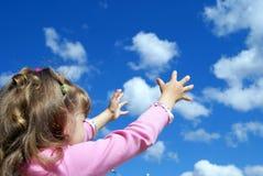 L'enfant attrape des mains d'un nuage deux Photographie stock