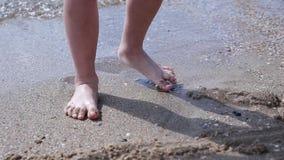 L'enfant aux pieds nus heureux ont l'amusement sur la promenade de plage La course de fille le long du ressac de mer par la pisci banque de vidéos