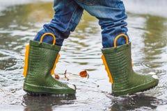 L'enfant avec des bottes de pluie saute dans un magma Image libre de droits
