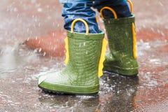 L'enfant avec des bottes de pluie saute dans un magma Photos libres de droits