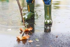 L'enfant avec des bottes de pluie saute dans un magma Photo stock