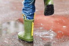 L'enfant avec des bottes de pluie saute dans un magma Photos stock