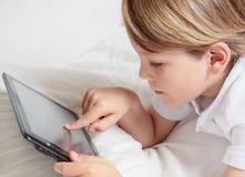 L'enfant avec des multimédia marquent sur tablette le PC. Photos stock