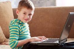 L'enfant avec l'ordinateur portatif image libre de droits