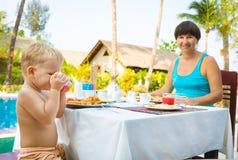 L'enfant avec la mère prennent un petit déjeuner Photo stock