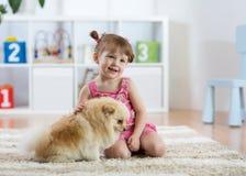 L'enfant avec le chien se reposant sur le plancher à la maison image libre de droits