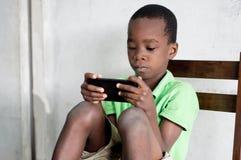 L'enfant avec le téléphone portable photographie stock