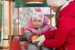 L'enfant avec son équitation de mère sur une glissière Image stock