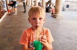 L'enfant boit du jus avec une paille photographie stock libre de droits