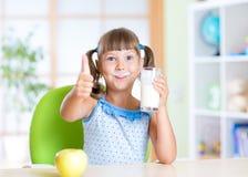 L'enfant boit du lait et de représentation pouce  Photographie stock