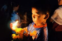 l'enfant bouddhiste de pèlerin de theravada mignon avec une bougie et la fleur flottent le radeau pendant une célébration sainte  images stock