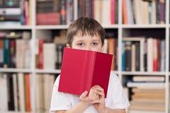 L'enfant cache le visage derrière le livre i image libre de droits