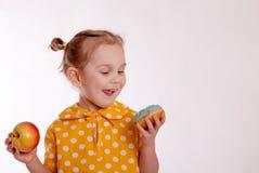 L'enfant choisit de manger doux ou sain image stock