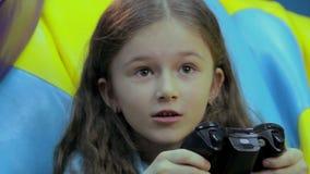 L'enfant a concentré le visage, dépendant à jouer des jeux vidéo, amusement clips vidéos