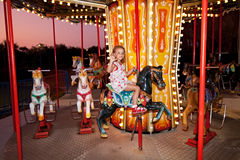 L'enfant conduit un carrousel Photos stock