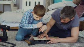 L'enfant curieux conduit la vis dans le morceau de bois avec le tournevis et son papa tient la feuille en bois et l'enseigne banque de vidéos