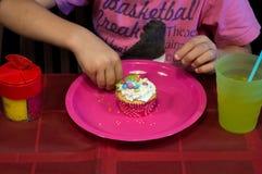 L'enfant décore un petit gâteau photo stock