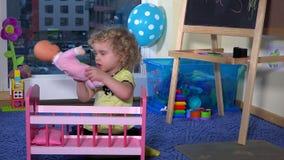 L'enfant d'enfant en bas âge fixent le bébé de jouet - poupée et balancent dans la huche banque de vidéos