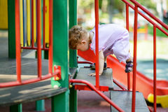 L'enfant d'une année monte les escaliers sur le terrain de jeu Image stock