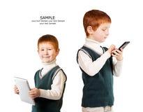 L'enfant d'une chevelure rouge mignon pose avec le PC et le smartphone de comprimé isola Photos libres de droits