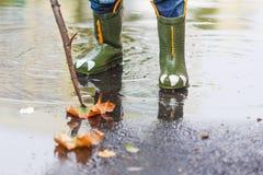 L'enfant dans des bottes de pluie saute dans un magma image libre de droits