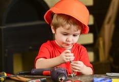 L'enfant dans le casque antichoc, casque jouant avec le sortilège se boulonne comme constructeur ou réparateur, handcrafting Enfa Image libre de droits