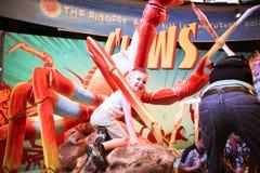 L'enfant dans le parc aquatique s'assied sur un grand crabe de jouet Image stock
