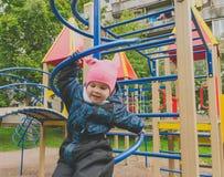 L'enfant dans le terrain de jeu en bas de l'arc en spirale Photos stock